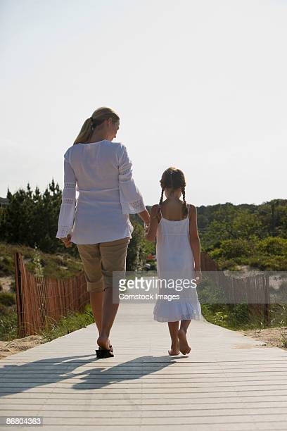 Mother and daughter walking along path
