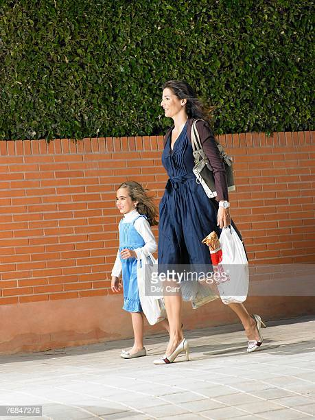 Mother and daughter  (5-7) walking along pavement with shopping bags, Alicante, Spain,
