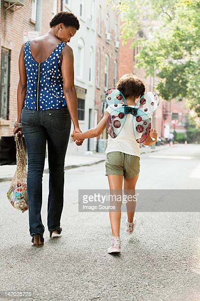 Mother and daughter walking along street, rear view