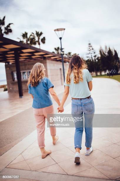 Mother and daughter walking and holding hands in the park