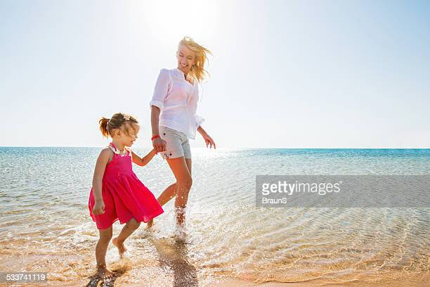 Mother and daughter walking at the beach.