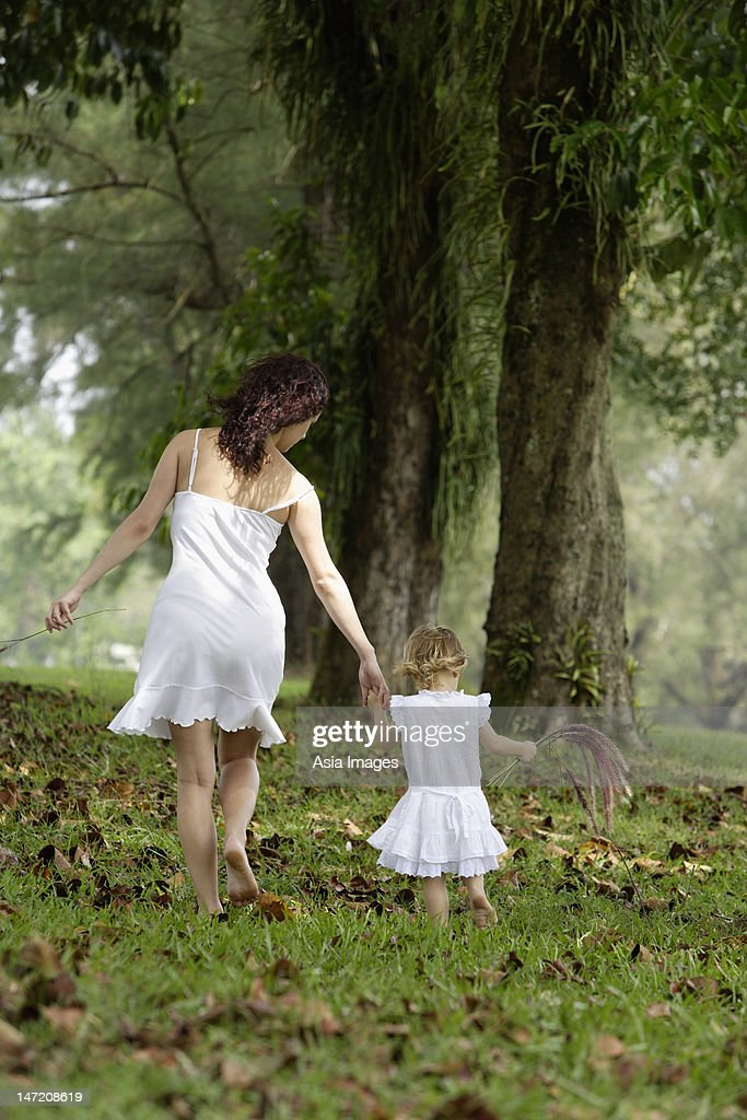 Mother and daughter walking away, wearing white : Stock Photo