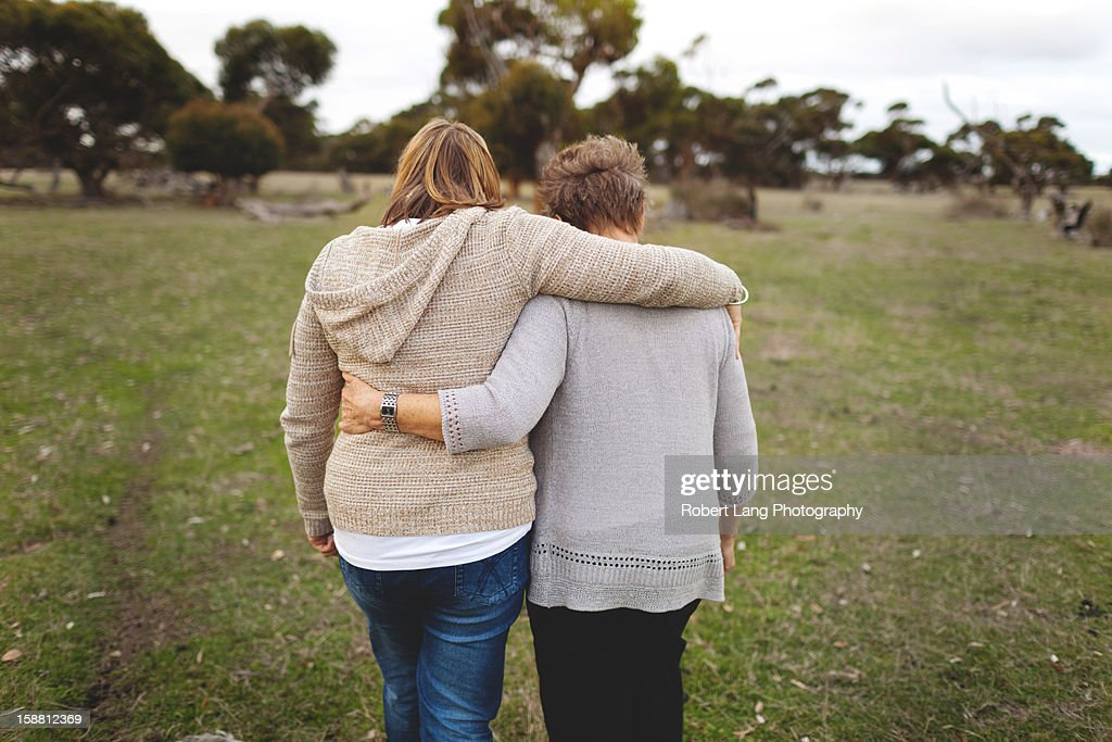 Mother and daughter walking embrace