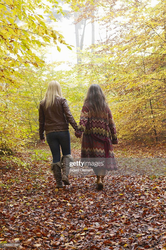 Mother and daughter walking in forest : Stock Photo