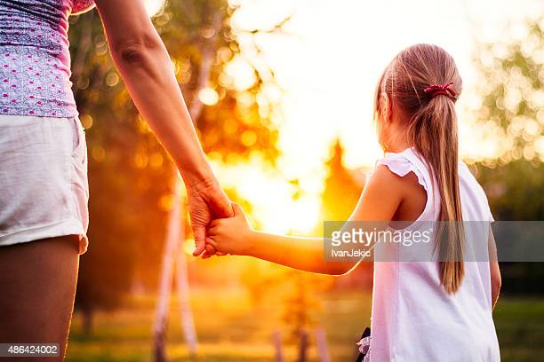 Mother and daughter walking in park at sunset