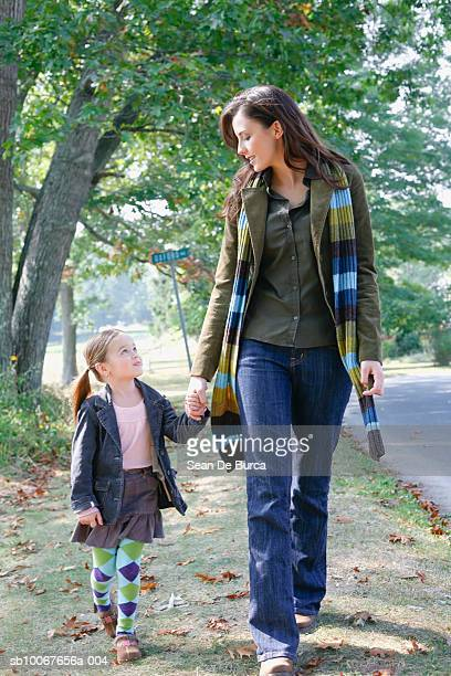 Mother and daughter (6-7) walking in park