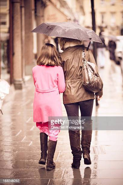 Mother and daughter walking in rain