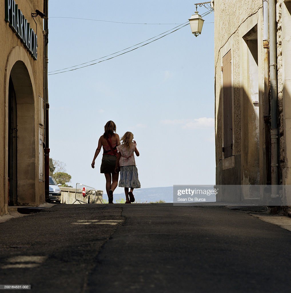 Mother and daughter (8-10) walking in street, rear view : Stock Photo