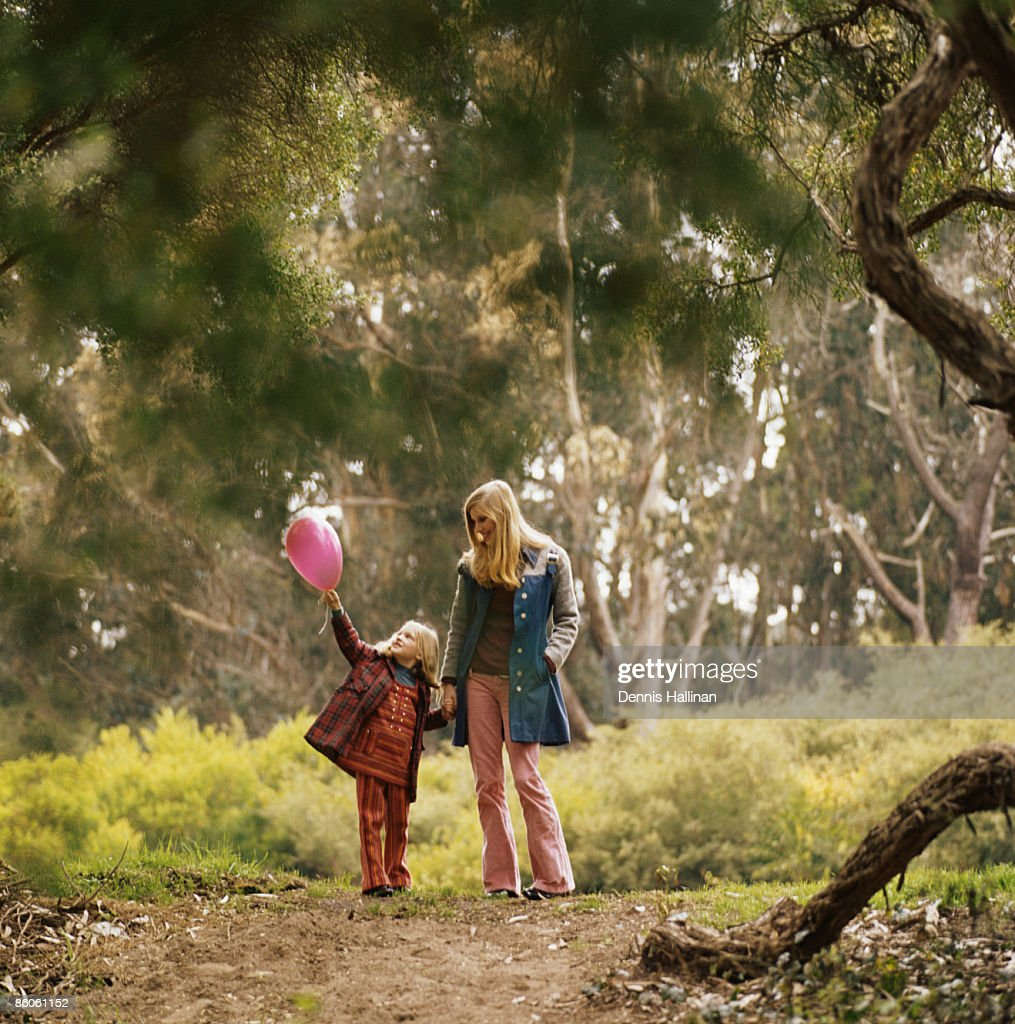 Mother and daughter walking in the woods : Stock Photo