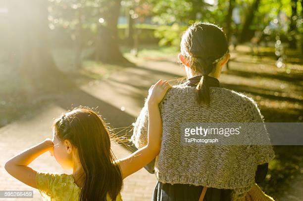 Mother and daughter walking into the sunset