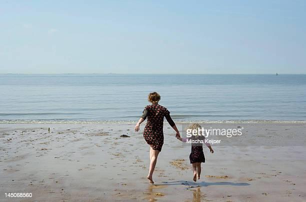 Madre e hija caminando en la playa