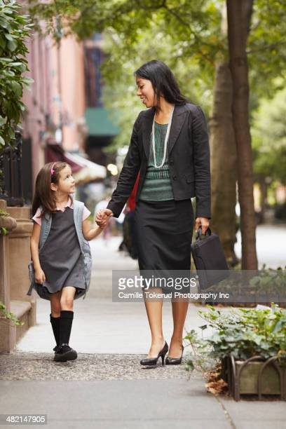 Mother and daughter walking on city street