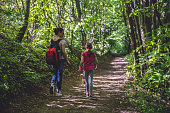Mother and daughter walking on path in woods and talking