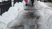 Mother and daughter walking on slushy slippery sidewalk, snow and ice melted, Montreal, Quebec, Canada