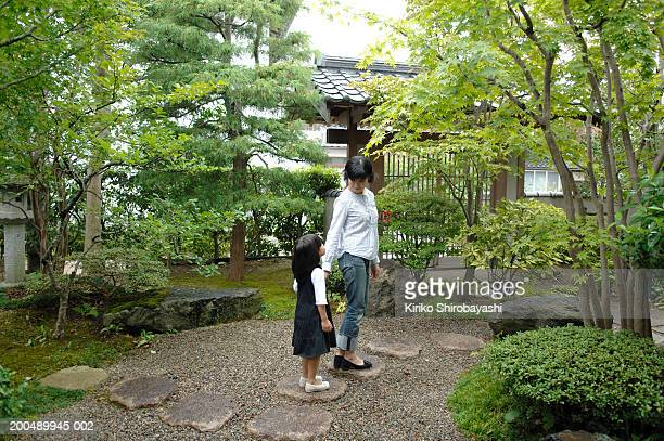 Mother and daughter (3-5) walking on stone steps in garden