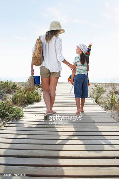 Mother and daughter (6-8) walking on wooden path to beach, rear view