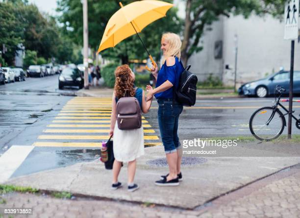 Moeder en dochter naar school lopen in de straat ochtend stad.