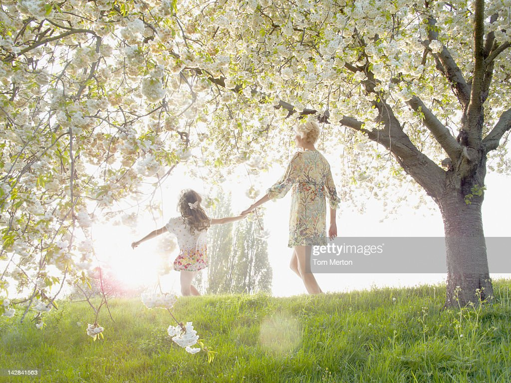 Mother and daughter walking under flowering tree : Stock Photo