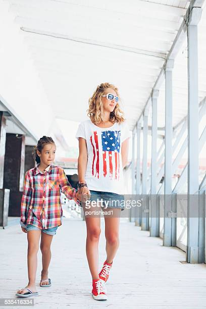 Mother and daughter walking under open shelder and holding hands