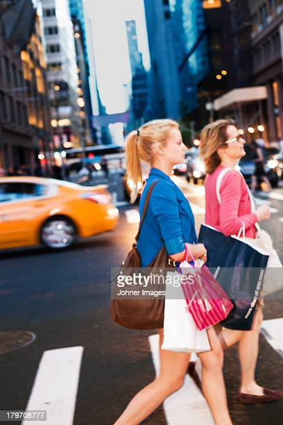Mother and daughter walking with shopping bags