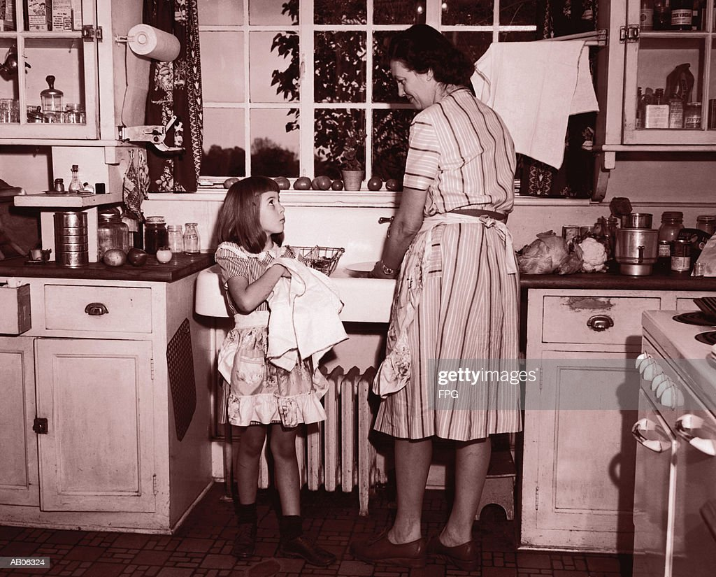 Mother and daughter (8-10) washing and wiping dishes (B&W sepia tone) : Stock Photo