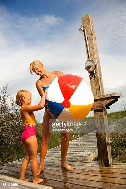 Mother and daughter washing beach ball at outdoor shower