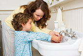 Mother and daughter washing their hands in bathroom
