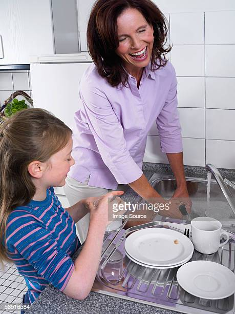 Mother and daughter washing up