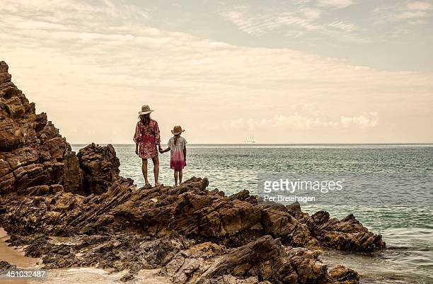 Mother and daughter watching a ship sail by