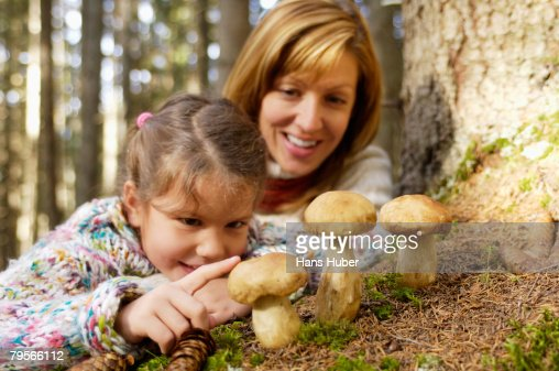 Austria, mother and daughter (6-7) watching ceps in forest