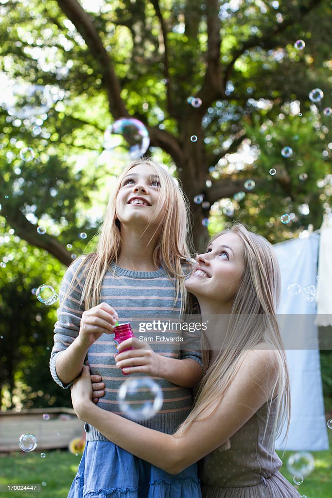 Mother and daughter watching floating bubbles in park : Stock Photo