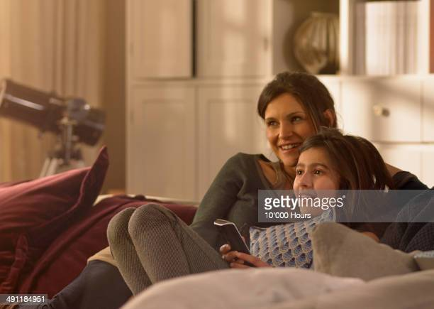 A mother and daughter watching television