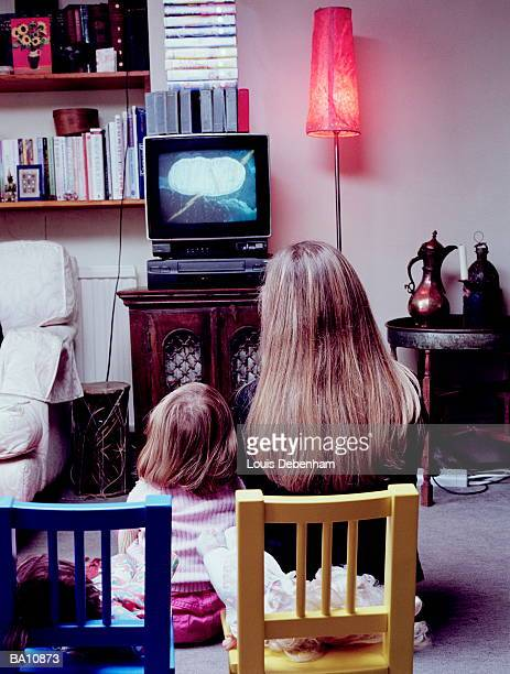Mother and daughter (2-4) watching television, rear view