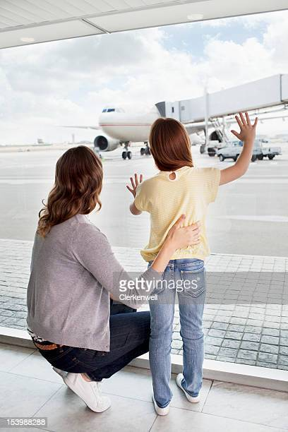 Mother and daughter waving at airplane in airport
