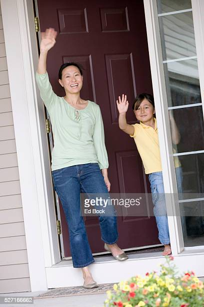 Mother and Daughter Waving from Front Door
