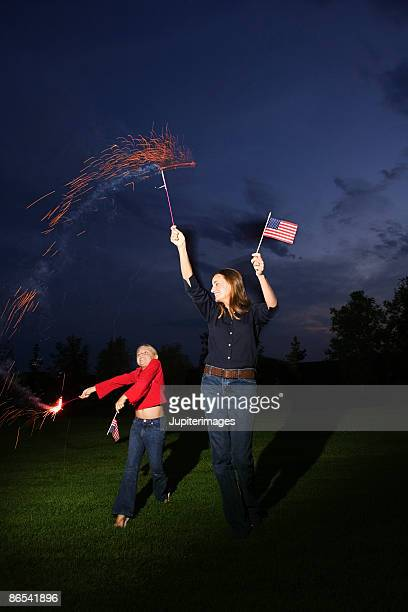 Mother and daughter waving sparklers and American flags