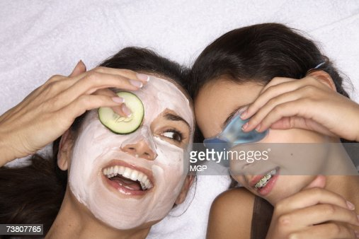 Mother and daughter (11-13) wearing face packs, close-up (overhead view)