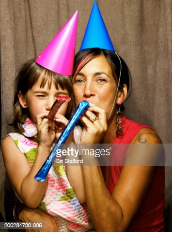 Mother and daughter (6-8) wearing party hats in photo booth : Stock Photo
