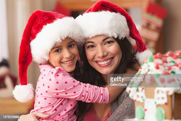 Mother and daughter wearing Santa hats and hugging