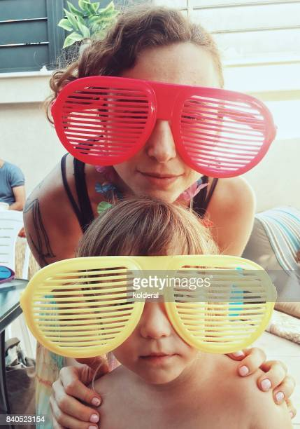 Mother and daughter wearing toy sunglasses