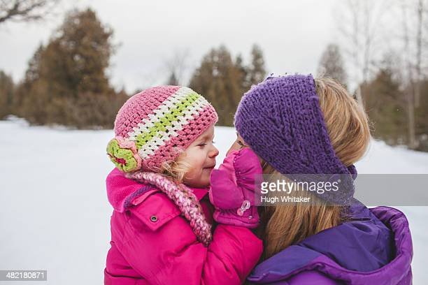 Mother and daughter wearing winter clothing, face to face in snow