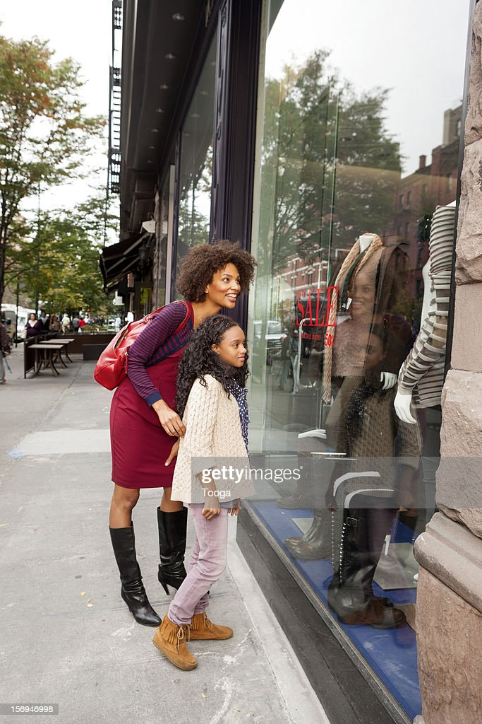 Mother and daughter window shopping in city : Stock Photo