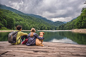 Mother and daughter with a small yellow dog resting on a pier and looking at lake and foggy mountains
