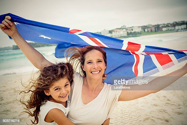 Mother and daughter with Australian flag at the beach, Australia