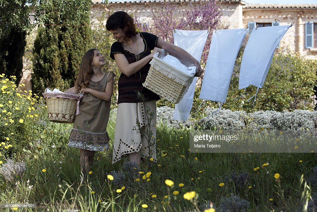 Mother and daughter (8-9) with baskets in domestic garden