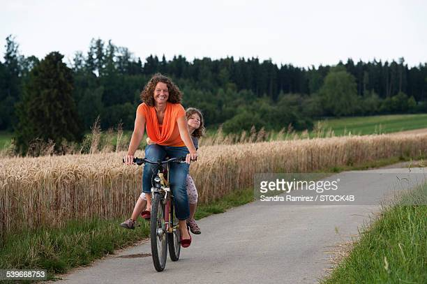Mother and daughter with bicycle on country lane