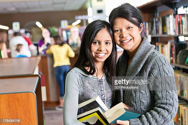 Mother and daughter with books in a library