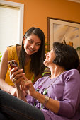 mother and daughter laughing with cell phone