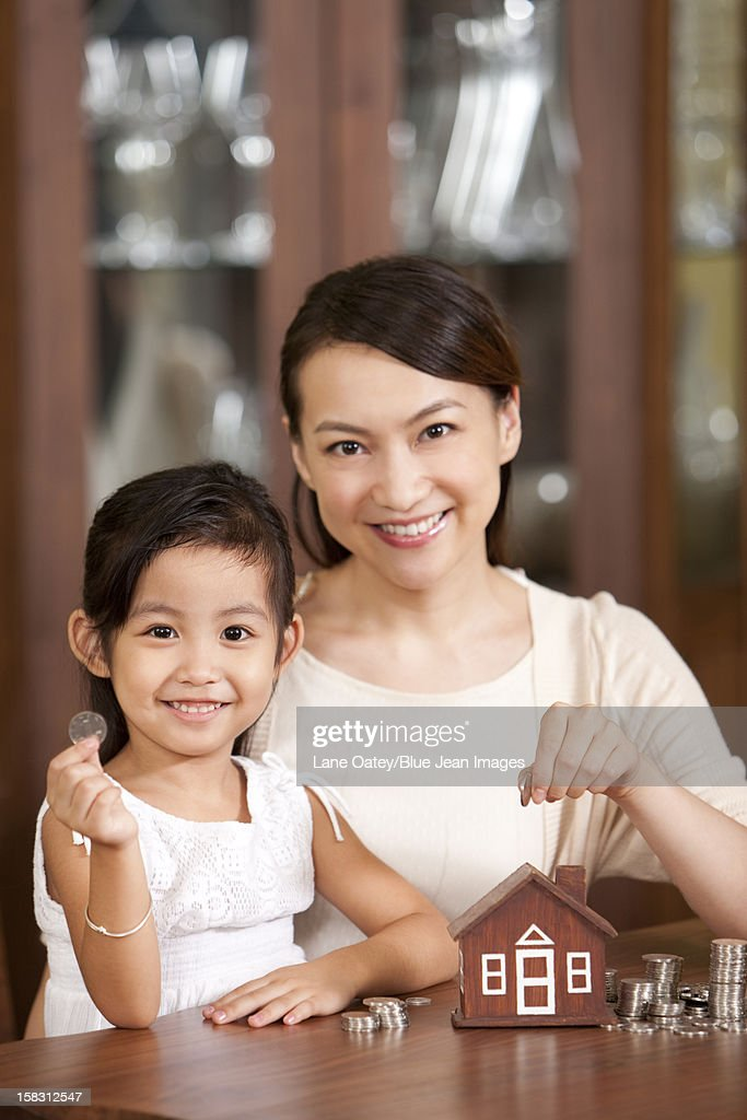 Mother and daughter with coin bank : Stock Photo