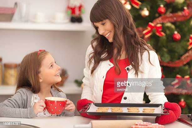 Mother and daughter with cookies by christmas tree.